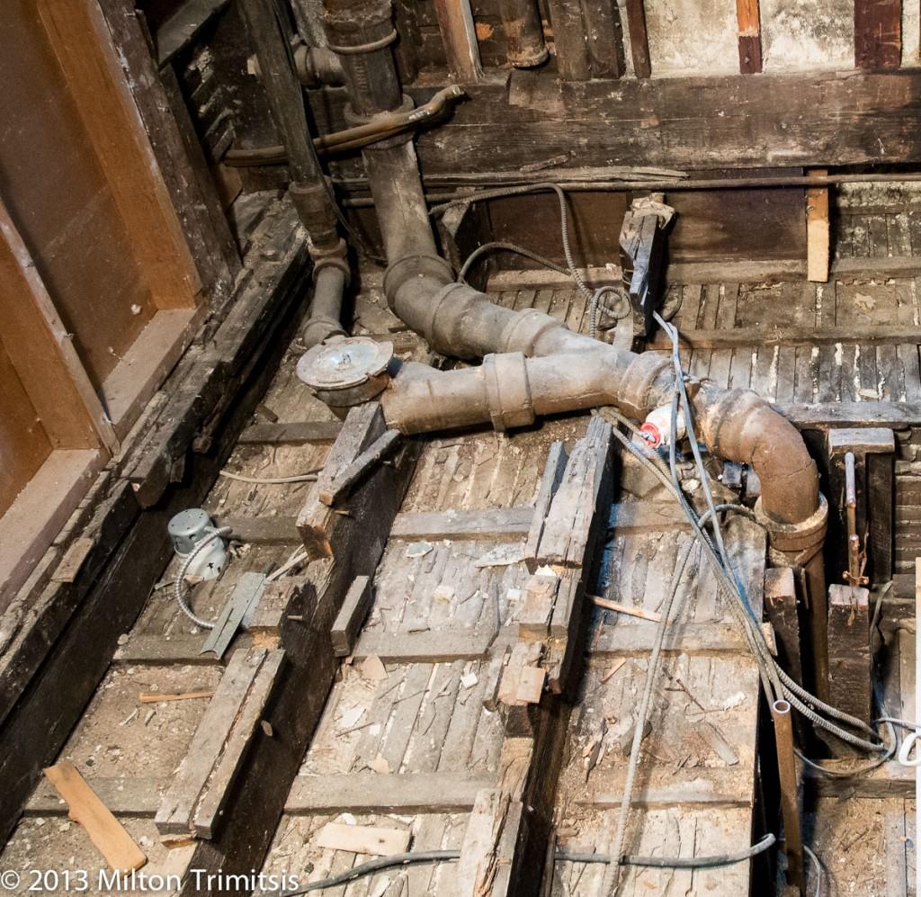 Cast iron waste line in bath floor with cut floor joists