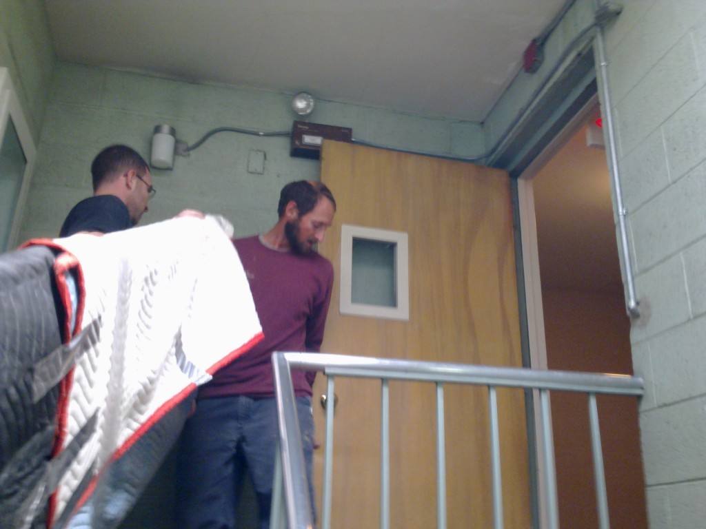 2 men carrying a tabletop up a narrow stairwell, at the top