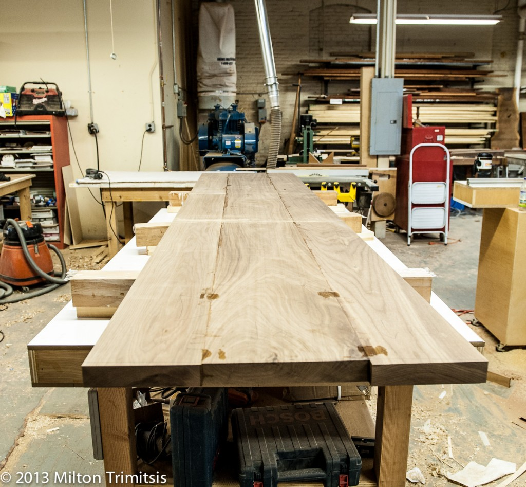 walnut boards in a woodshop being glued into a tabletop