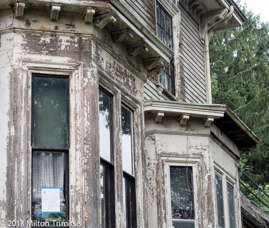 Detail of ornate brackets on old Victorian house, in need of repair