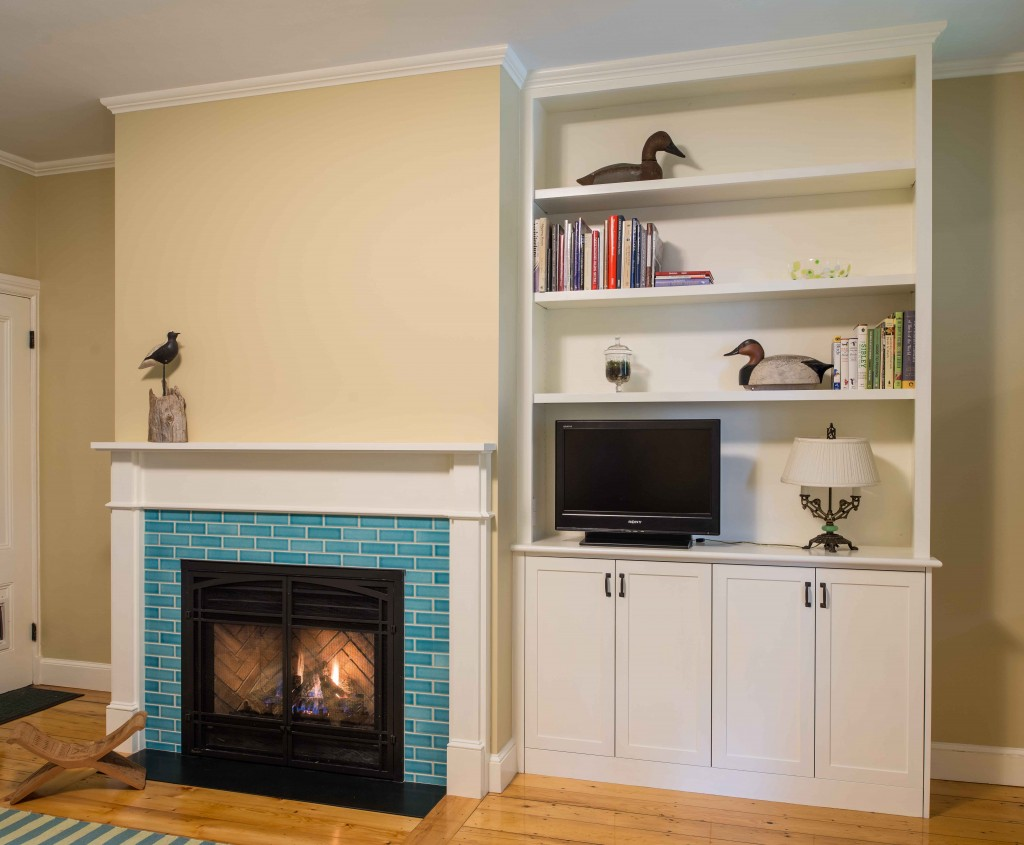 wood mantel, gas fireplace, tiled surround, and built-in bookcase