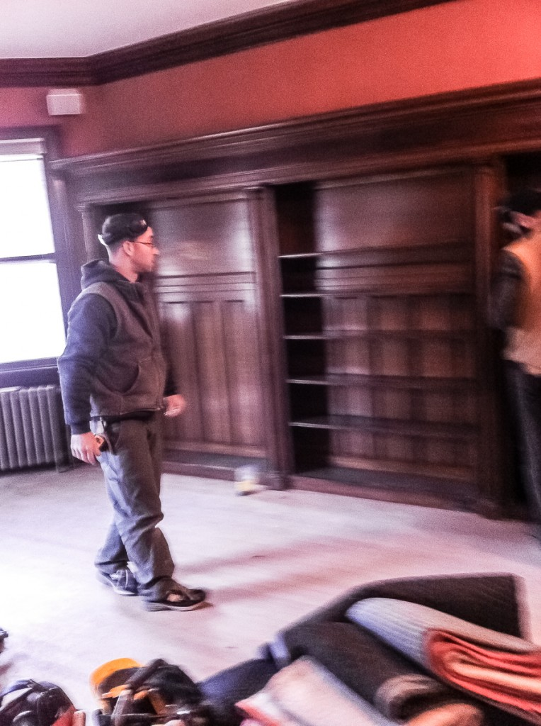 Carpenter preparing to dismantle oak library cabinets