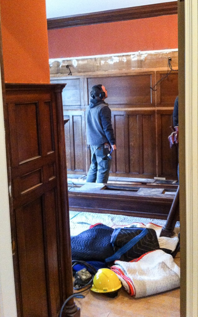 two carpenters dismantling oak library cabinets