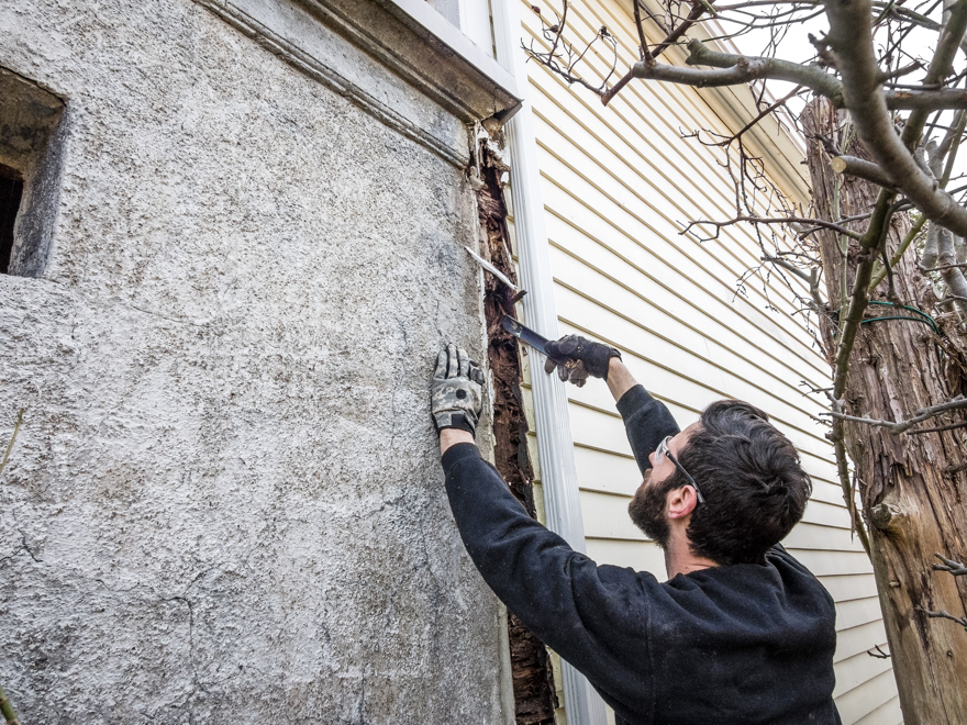 Carpenter burying his pry bar into a rotten corner post
