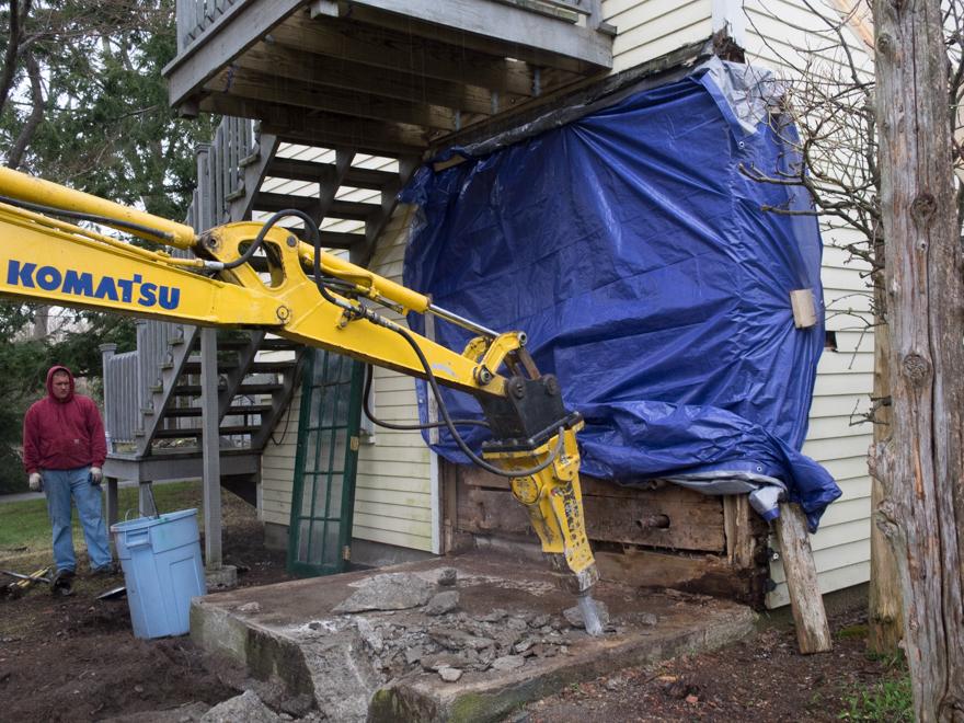 Using a hydraulic hammer to break apart concrete slab and foundation