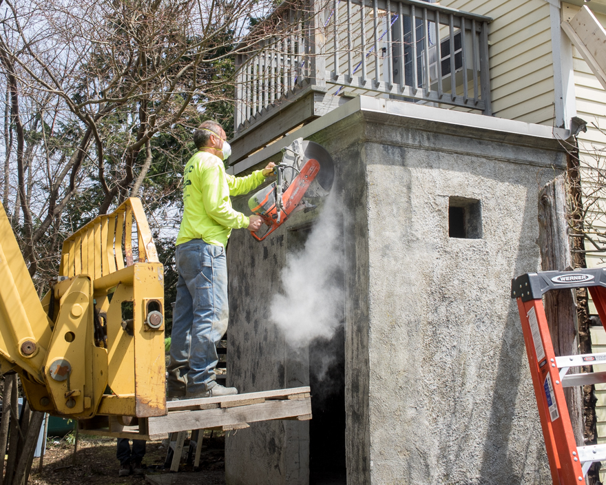 Man using concrete-cutting saw to make access hole in concrete wall